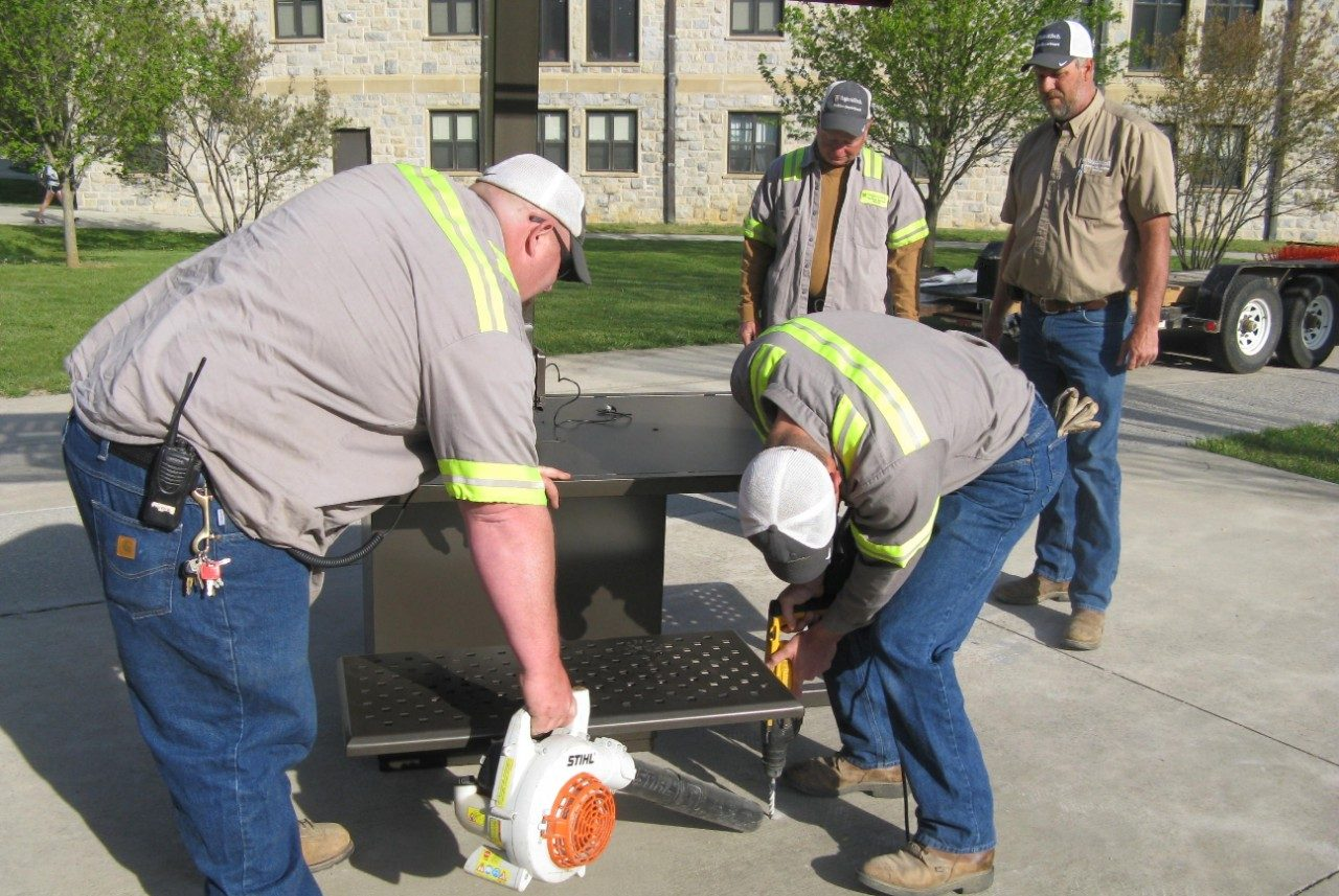 Facility employees drilling a hole in concrete to secure the solar table.