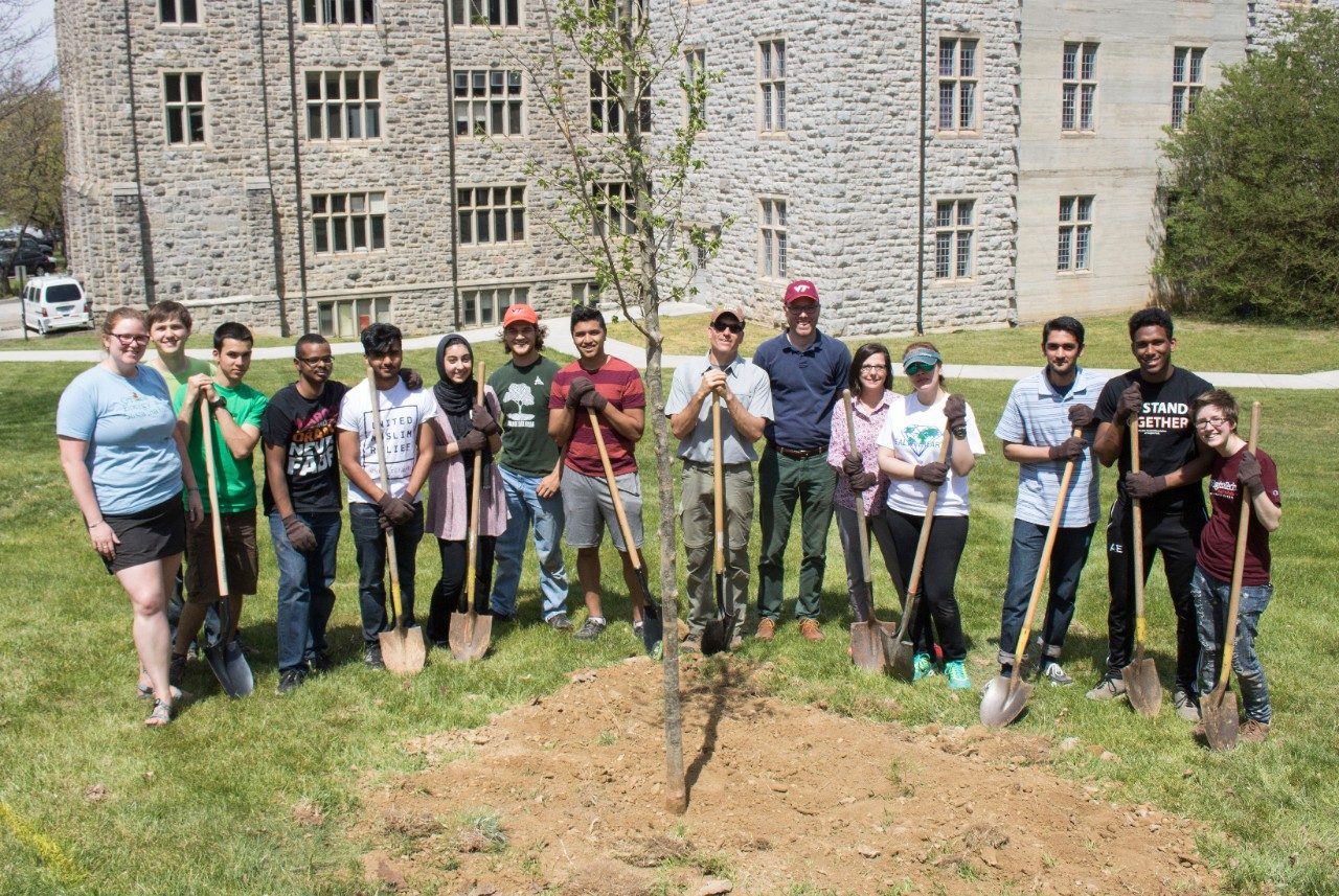 Students and employees posing behind a newly planted sapling.
